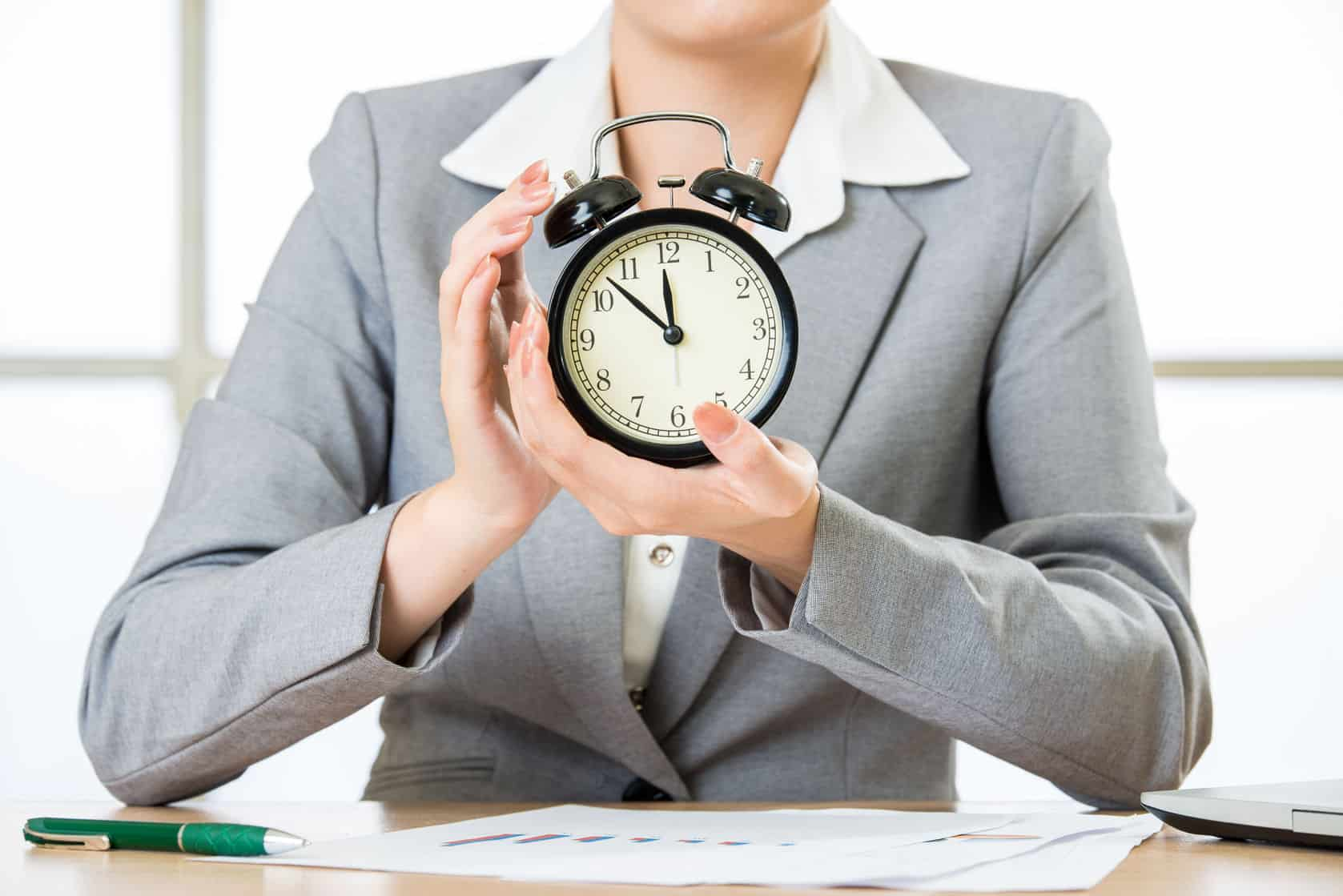 58383827 - business woman holding clock in office